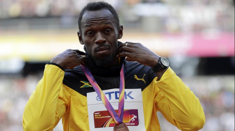 Jamaica's Usain Bolt wears the bronze during the medal ceremony for the Men's 100m during the World Athletics Championships in London. (Photo: AP)