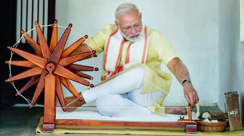 A file photo of Prime Minister Narendra Modi spinning a charkha at the Sabarmati Ashram. (Photo: PTI)
