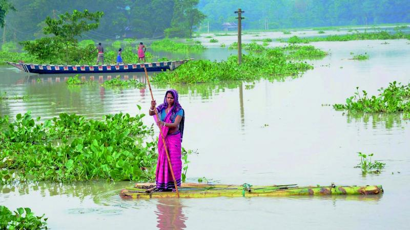 Flood-affected villagers commute to safer places using boats in Assam's Morigaon district. (Photo: PTI)