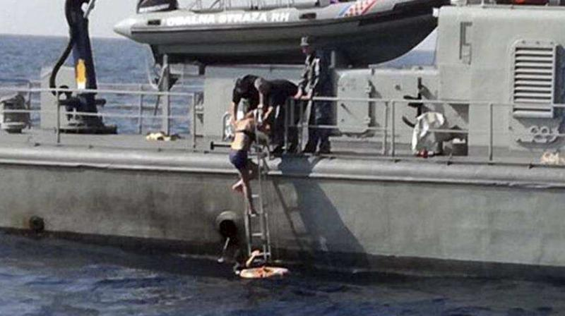 In this photo provided by the Croatian Defence Ministry, a woman who identified herself as Kay from England, climbs aboard a Croatian Coast Guard ship some 90 kilometres from the Croatian coast. (Photo: AP)