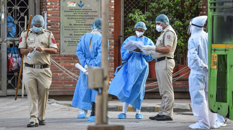 Medics wearing protective suits seen in the premises of LNJP hospital while members of Tablighi Jamaat are shifted from hospital to quarantine centre during nationwide lockdown in Delhi. PTI photo