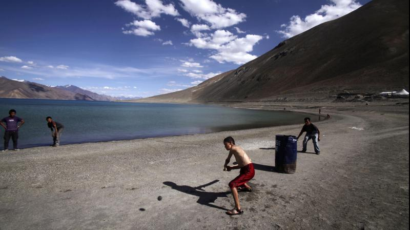 In this July 22, 2011 file photo, children play cricket by the Pangong Lake, near the India-China border in Ladakh, India. Indian officials say Indian and Chinese soldiers are in a standoff in the remote Ladakh region, with the two countries amassing soldiers and machinery near the tense frontier. The officials said the standoff began in early May when large contingents of Chinese soldiers entered deep inside Indian-controlled territory at three places in Ladakh, erecting tents and posts. (AP)