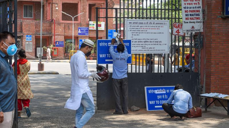 A worker hangs a notice on the main gate of the LNJP Hospital in New Delhi. (PTI)