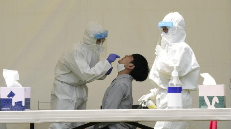 A medical worker takes a nasal sample from a man during a COVID-19 testing at a makeshift testing site at the National Assembly in Seoul, South Korea, Thursday, July 15, 2021. (AP/Ahn Young-joon)