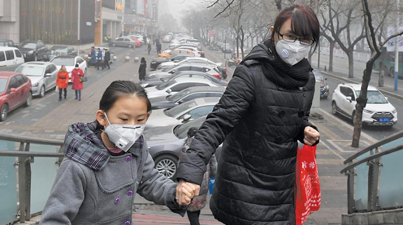 A file photo shows a mother and daughter climbing a pedestrian overpass on a heavily polluted day in Shijiazhuang, in Hebei province, China. (Photo: AFP)
