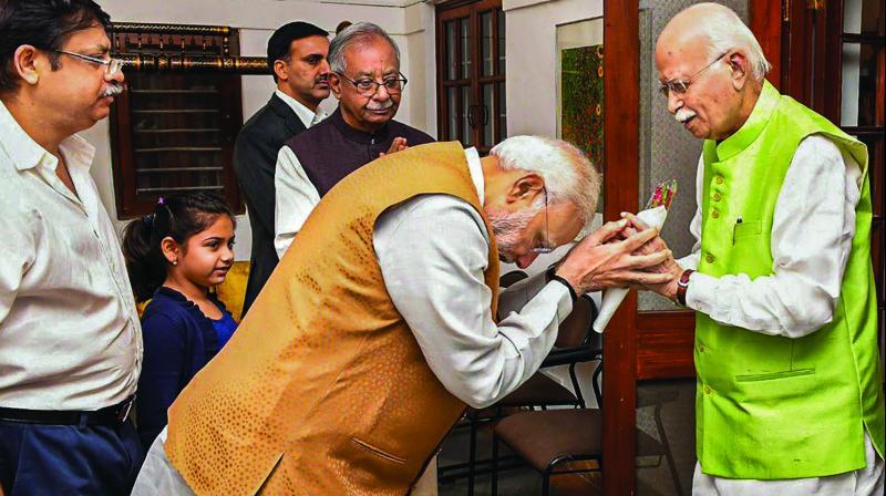 Prime Minister Narendra Modi greets senior BJP leader L.K. Advani on his 91st birthday at his Prithiviraj Road residence in New Delhi. (Photo: PTI)