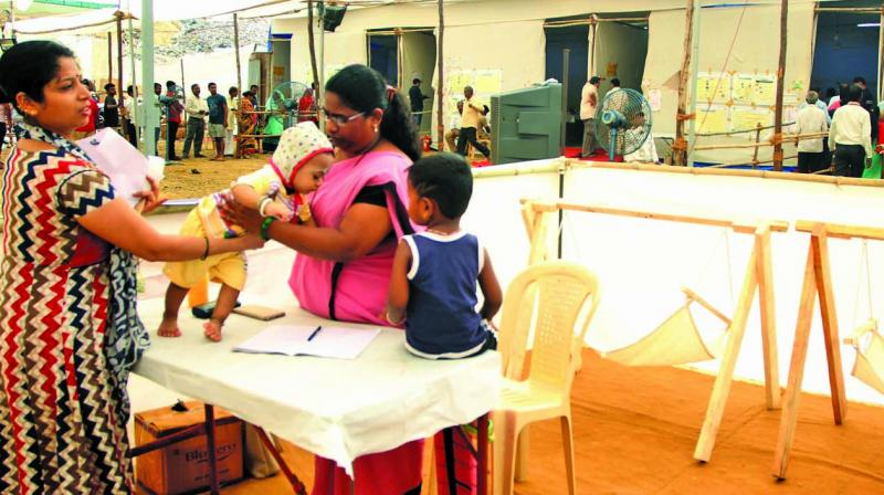 A voter hands over her child to an anganwadi worker.