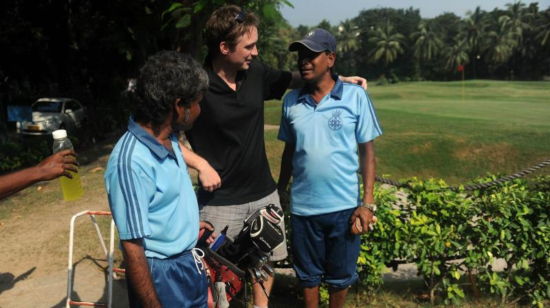 File photo of a golfer interacts with caddies before teeing off in Mumbai. AFP Photo