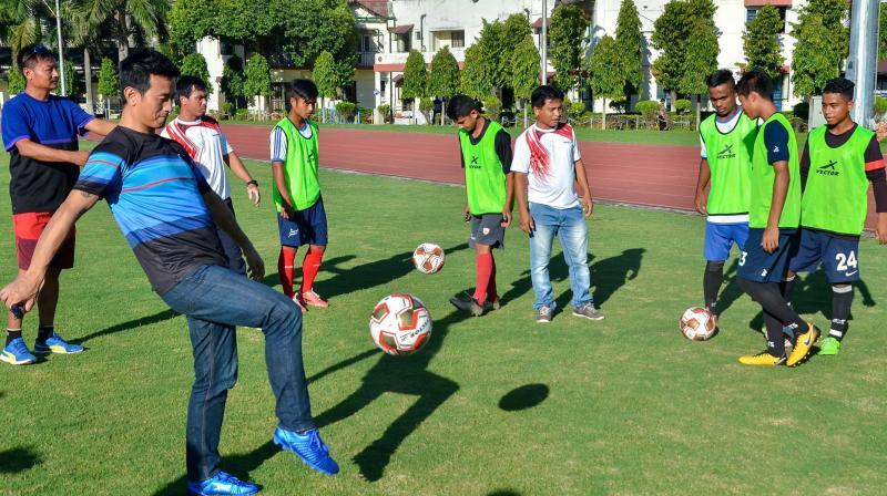 Bhaichung Bhutia plays with aspiring footballers at Paltan Bazar in Guwahati. PTI Photo