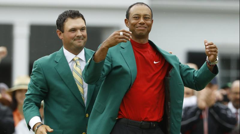 Patrick Reed helps Tiger Woods with his green jacket after Woods won the Masters golf tournament on April 14 last year in Augusta, Georgia. AP Photo