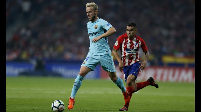 Barcelona's Ivan Rakitic (L) runs with the ball ahead of Atletico Madrid's Angel Correa during a Spanish La Liga match. AP Photo