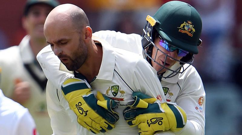 Nathan Lyon celebrates his wicket with captain and wicket-keeper Tim Paine. AFP Photo