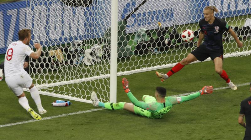 Harry Kane (L) slots home from a difficult angle for England against Croatia at the 2018 World Cup. AP Photo
