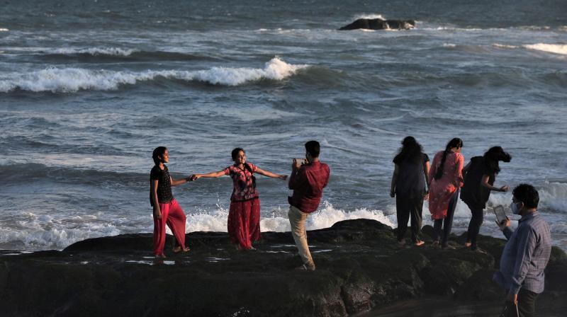 Tourists take pictures at Ramakrishna beach on the Bay of Bengal coast in Visakhapatnam, Andhra Pradesh. (Photo: AP)
