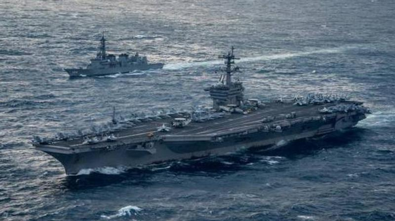 Aircraft carrier USS Carl Vinson (CVN 70), foreground, transits the East China Sea with the Japan Maritime Self-Defense Force Murasame-class destroyer JS Samidare. (Photo: AFP)