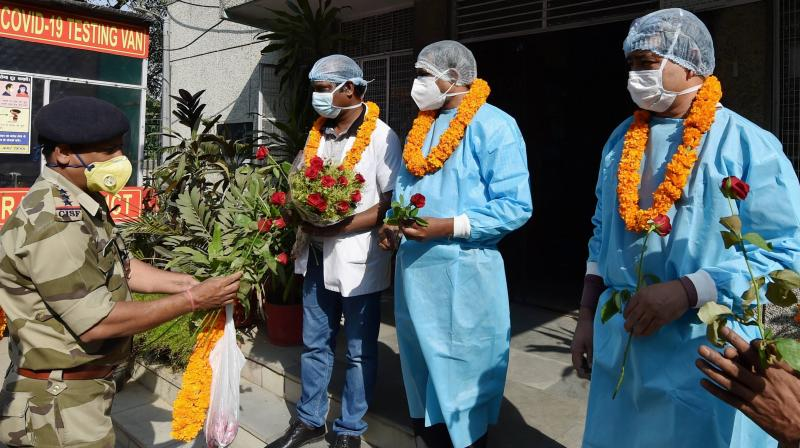 CISF officers and jawans shower flower petals on doctor and health workers during felicitation program to express gratitude towards their contribution in the fight against the coronavirus, at SDMC Urban Public Health Centre, Daryaganj in New Delhi, Saturday, Oct. 31, 2020. (PTI Photo)