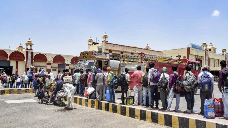Migrants stand in a queue on a hot sunny day at Lalgarh Junction to board a special train to Bihar, during the ongoing COVID-19 lockdown, in Bikaner. PTI Photo