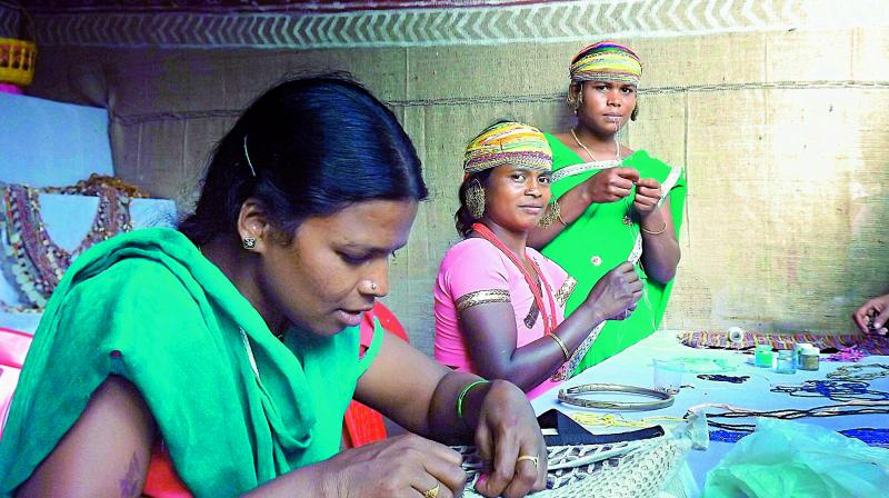 Tribal women working together on hand-made bags.