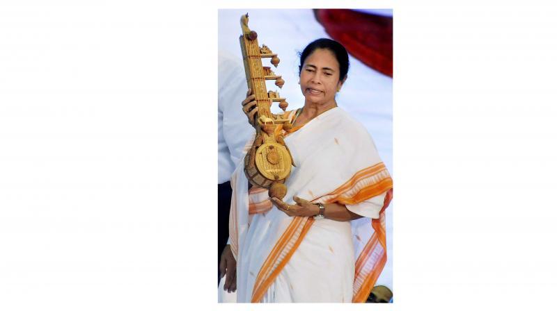 West Bengal Chief Minister Mamata Banerjee being presented a memento by the Jain community people during Acharya Mahashramanji's Ahimsha Yatra Conference at Netaji Indoor Stadium in Kolkata. (Photo: PTI)