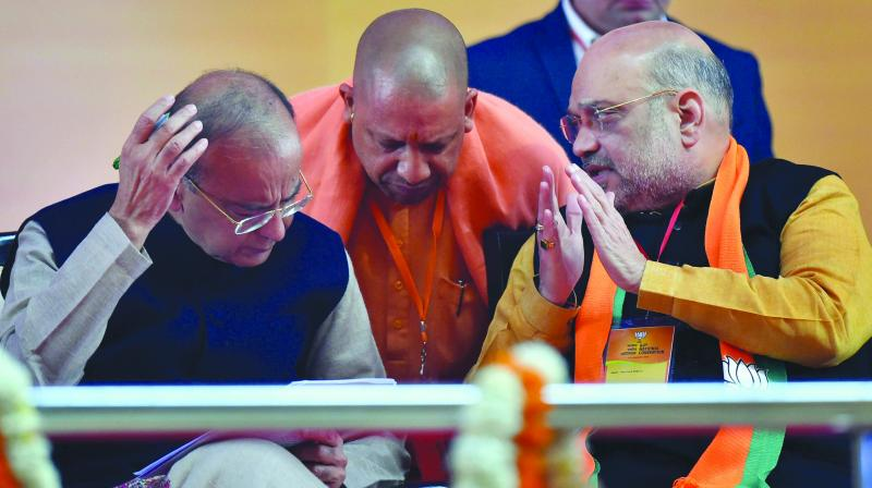 BJP president Amit Shah speaks with senior party leaders Arun Jaitley and Yogi Adityanath at Ramlila Ground in New Delhi. (Photo: PTI)