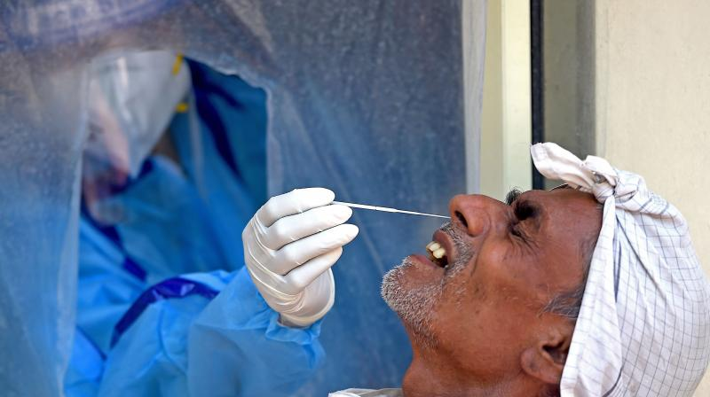 A health official wearing a Personal Protective Equipment (PPE) suit collects a swab sample from a man to test for the COVID-19 coronavirus, at a temporary testing facility in New Delhi. AP Photo