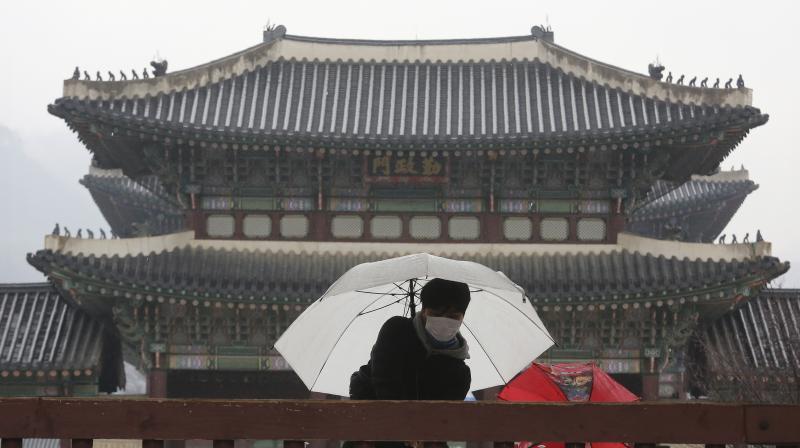 A man waring a face mask uses a hand sanitizer at the Gyeongbok Palace, the main royal palace during the Joseon Dynasty, in Seoul, South Korea. AP Photo