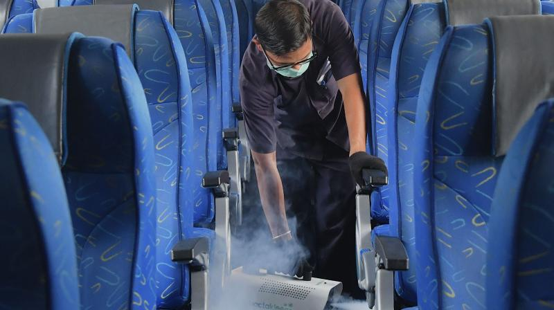 A worker fumigates the interiors of a Karnataka interstate transport bus to prevent the spread of the COVID-19 coronavirus in Bangalore. The state government is considering a total ban on interstate bus services.(AFP)