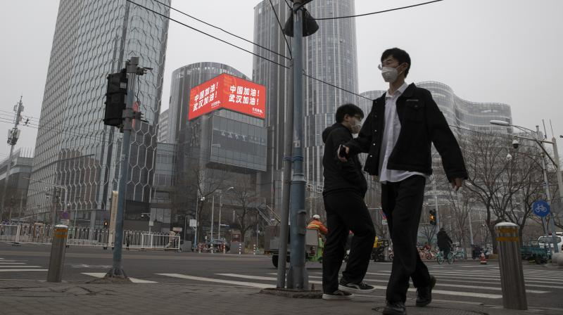 Residents walk past a retail and office district with a screen showing propaganda which reads 'Go China! Go Wuhan' as businesses slowly restart in Beijing. AP photo
