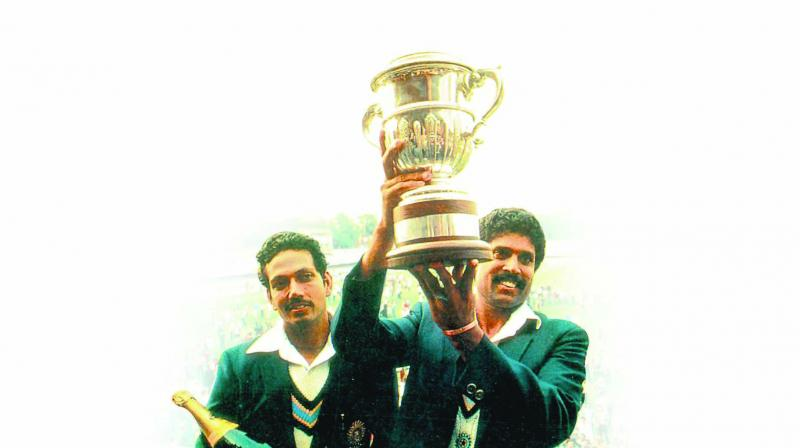 India skipper Kapil Dev holds the World Cup aloft as Mohinder Amarnath looks on.