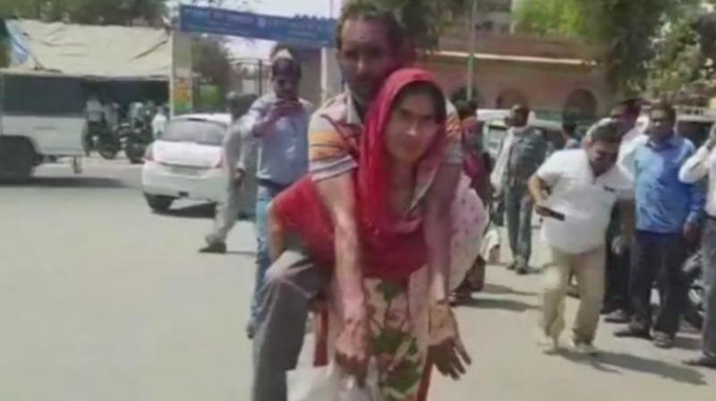 Vimla Devi carrying her husband Badan Singh on her back in Mathura. (Photo: ANI | Twitter)