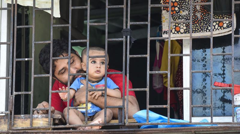 A man and a child look peek the window of their house at Dharavi, which has been sealed by the Brihanmumbai Municipal Corporation. (PTI)
