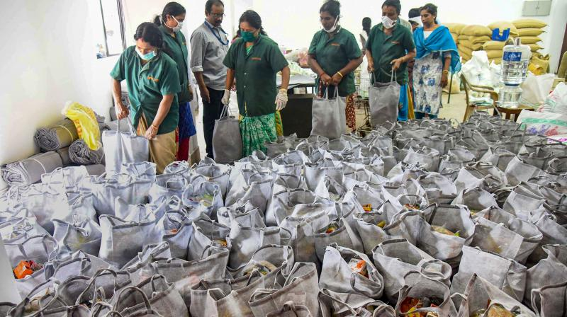 Workers arrange sacks containing essential supplies provided by the government during the current nationwide lockdown. (PTI)