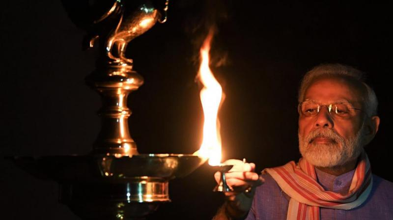 This image posted on prime minister Narendra Modi's Twitter account shows him lighting an oil lamp to mark the country's fight against the Covid-19 pandemic on Sunday, April 5, 2020.(AP/Twitter)
