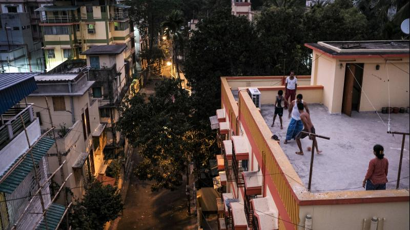A family plays football on the roof of their apartment during the ongoing coronavirus lockdown in Kolkata, on April 2, 2020. (AP)