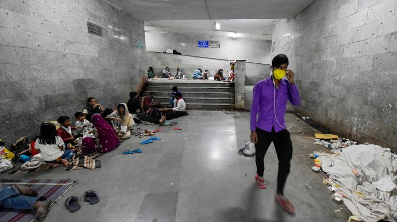 Patients discharged from the All India Institute of Medical Sciences (AIIMS) in New Delhi ,and their attendants take refuge amidst unhygienic conditions in a subway near the hospital as the nationwide lockdown left them no means of transport to go back home. (PTI)
