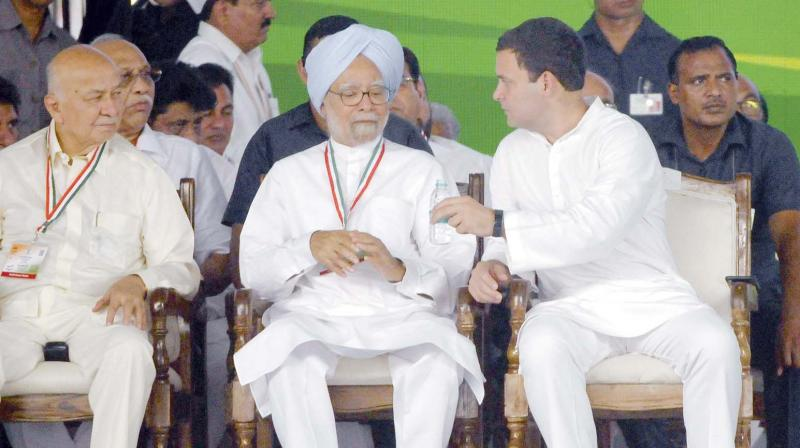 Congress president Rahul Gandhi offers water to former PM Manmohan Singh as Sushilkumar Shinde looks on during a rally in New Delhi. (Photo: Pritam Bandyopadhyay)