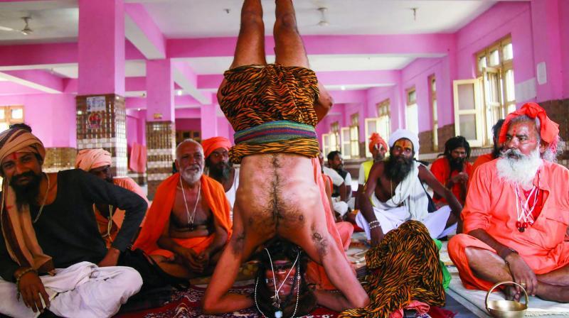 A sadhu performs yoga asanas at a temple ahead of International Yoga day in Jammu on Saturday. (Photo: PTI)