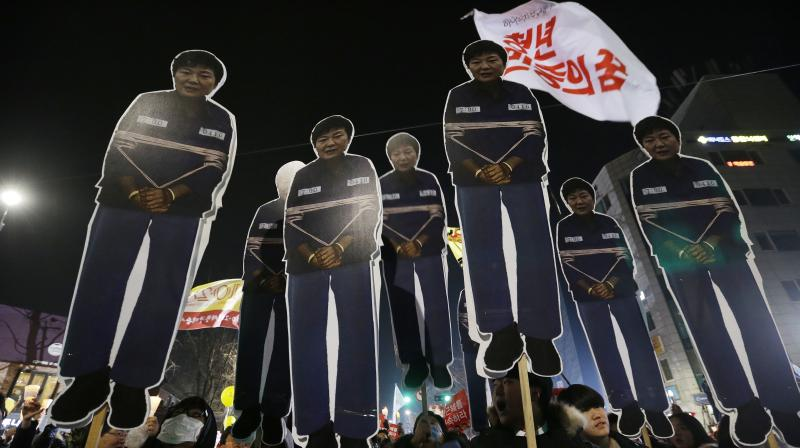 Protesters hold cutouts of South Korean President Park Geun-hye as they march toward the presidential house during a rally calling for Park to step down in Seoul, South Korea. (Photo: AP)