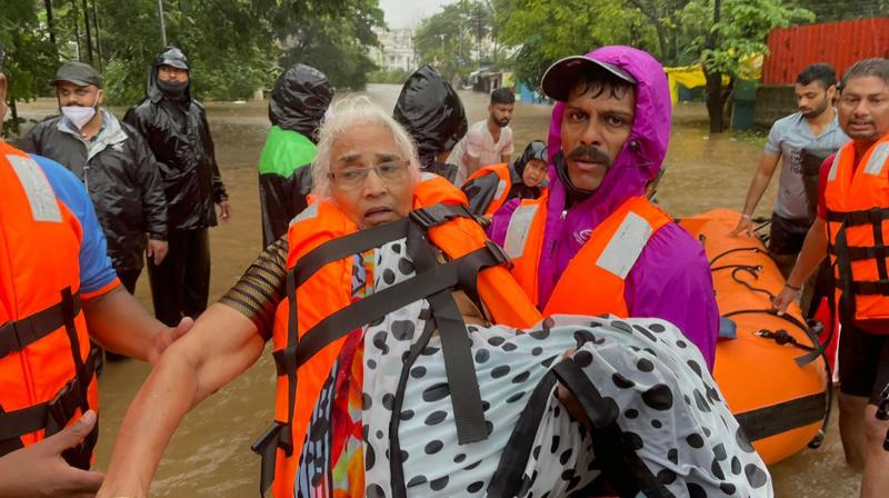 A National Disaster Response Force personnel rescues an elderly woman stranded in floodwaters in Kolhapur, in the western Indian state of Maharashtra, Friday, July 23, 2021. (Photo:AP)