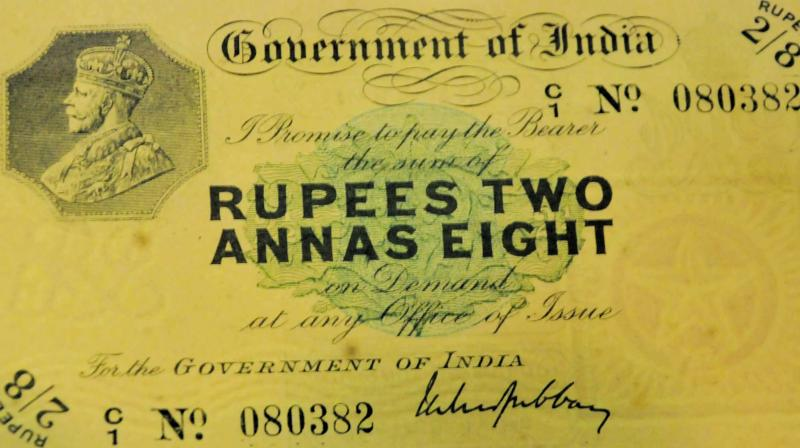 A one-and-a-half rupee note on display; A silver coin with a Swastika motif.