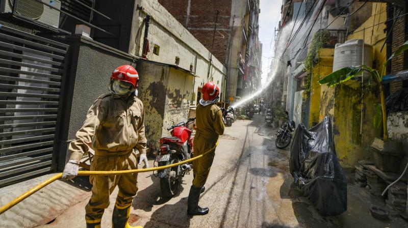 Firefighters spray disinfectants at a locality near Nizamuddin during the nationwide lockdown to curb the spread of coronavirus, at Bhogal in New Delhi. PTI Photo