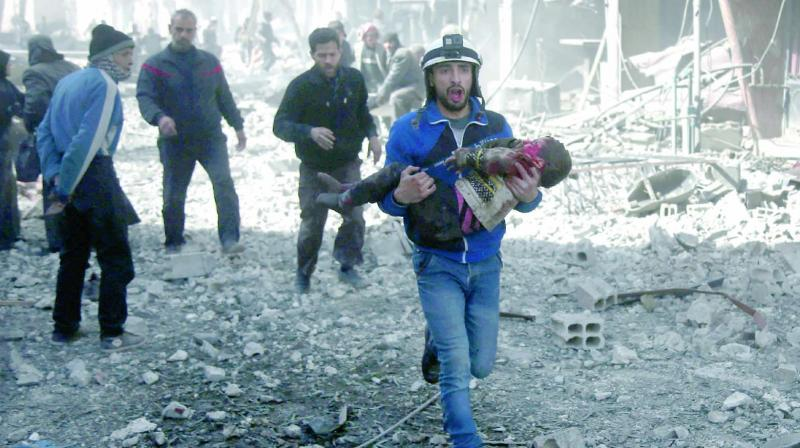 A Syrian civil defence member carries an injured child rescued following government bombings in the rebel-held town of Hamouria, on the outskirts of Damascus, on Monday. (Photo: AFP)