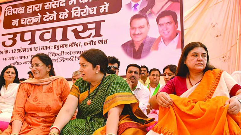 Union ministers Smriti Irani and Maneka Gandhi sit on a day-long protest in New Delhi on Thursday against the disruption of Parliament proceedings by the Opposition. (Photo: G.N. Jha)