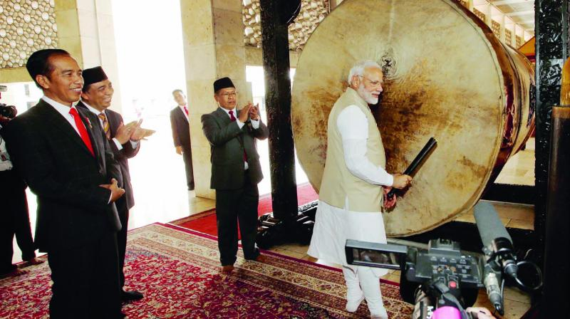 Prime Minister Narendra Modi pauses after hitting a 'bedug,' a large drum traditionally hit as a prelude to the call for prayer, as Indonesian President Joko Widodo (left) looks on during their tour at the Istiqlal Mosque, Southeast Asia's largest mosque, in Jakarta on Wednesday. (Photo: AP)