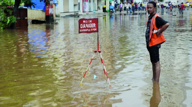 A BMC worker stand guard near a manhole at a waterlogged street near Hindmata, Parel.