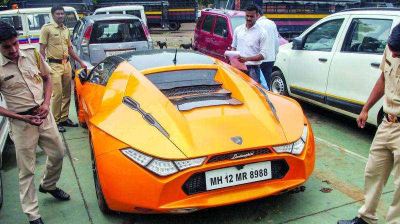 Police personnel investigate the seized Lamborghini of main accused in the cryptocurrency scam. (Photo: PTI)