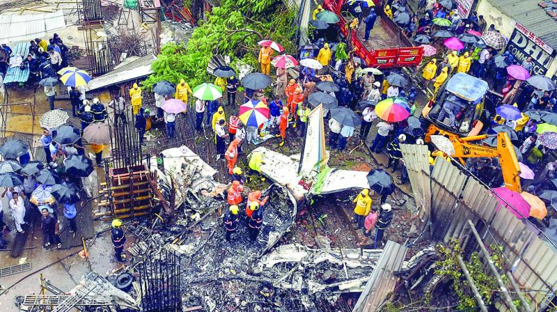 Rescue personnel and locals stand near the debris of the chartered plane that crashed in Ghatkopar's Jivdaya Lane, killing 5 people, in Mumbai on Thursday. (Photo: PTI)