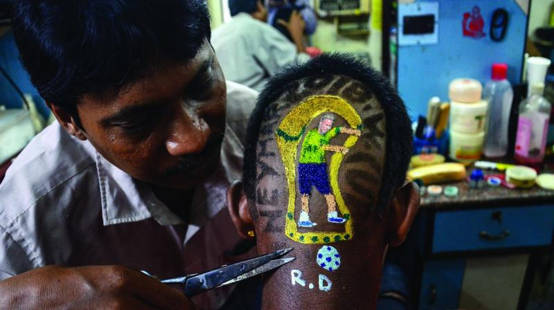 A barber trims the hair of a Brazil football team fan after the team won a match against Mexico during World Cup 'Round of 16', as FIFA fever grips the country, in Kolkata. (Photo: PTI)
