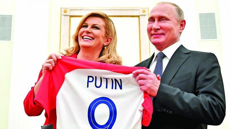Croatia President Kolinda Grabar Kitarovic (left) presents a T-shirt to her Russian counterpart Vladimir Putin. (Photo: AP)