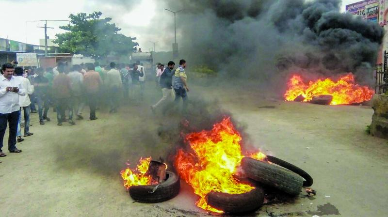 Smoke billows from a burning tyre during a protest rally where agitators demanded reservation for Marathas at Neknoor village in Beed. (Photo: PTI)